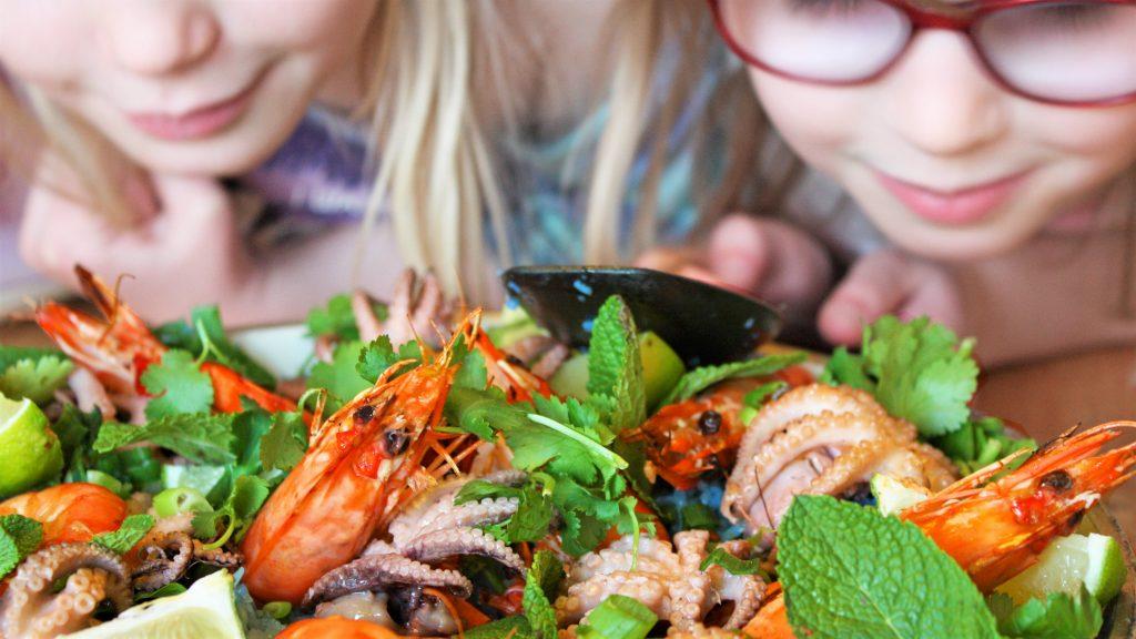 Barn tittar på ris med skaldjur